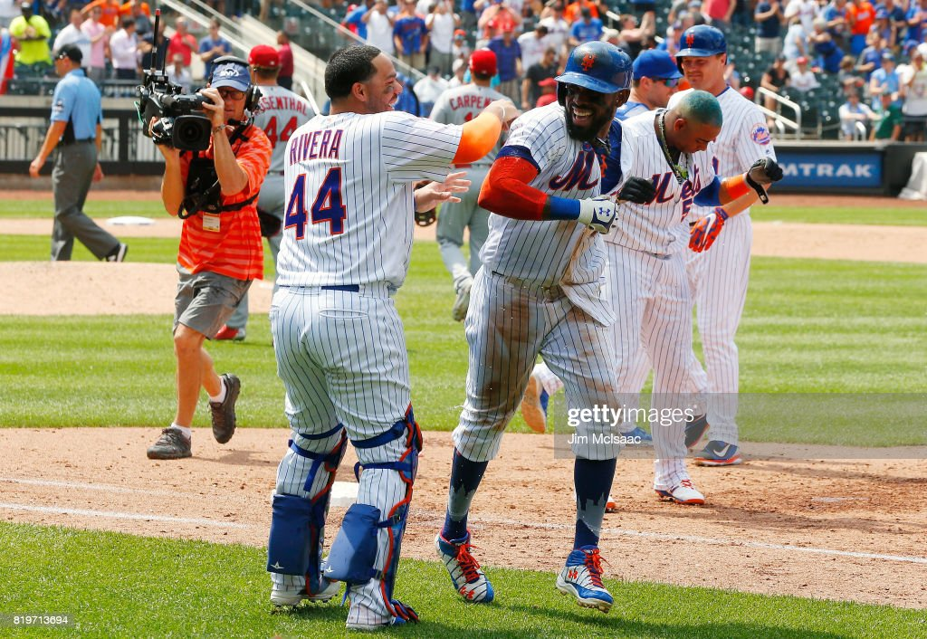 Jose Reyes #7 of the New York Mets celebrates his ninth inning game-winning infield base hit against the St. Louis Cardinals with teammate Rene Rivera #44 on July 20, 2017 at Citi Field in the Flushing neighborhood of the Queens borough of New York City.