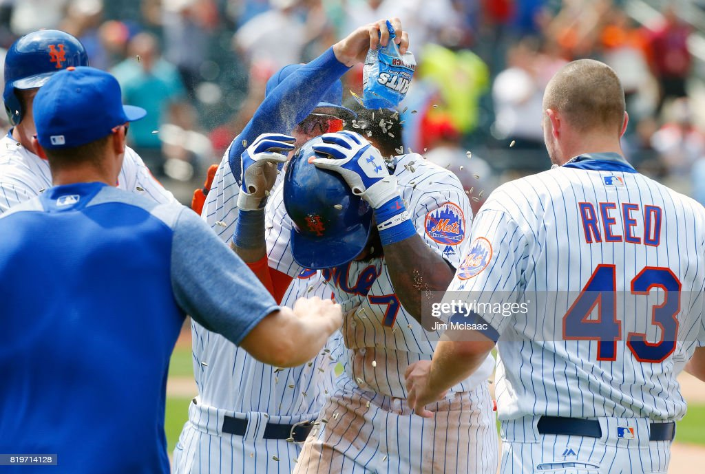 Jose Reyes #7 of the New York Mets celebrates his ninth inning game-winning infield base hit against the St. Louis Cardinals with his teammates on July 20, 2017 at Citi Field in the Flushing neighborhood of the Queens borough of New York City.
