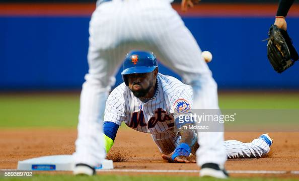 Jose Reyes of the New York Mets dives safely into third base during the first inning after a throwing error commited by the San Diego Padres at Citi...
