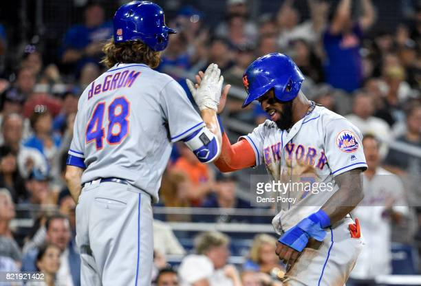 Jose Reyes of the New York Mets is congratulated by Jacob deGrom after scoring during the eighth inning of a baseball game against the San Diego...