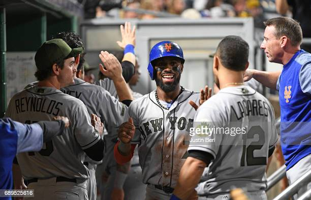 Jose Reyes of the New York Mets is greeted by teammates in the dugout after coming around to score on an RBI double by Jay Bruce in the fifth inning...