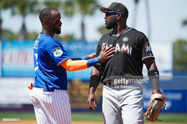 Jose Reyes of the New York Mets visits with Marcell Ozuna of the Miami Marlins in between innings of a Grapefruit League spring training game at...