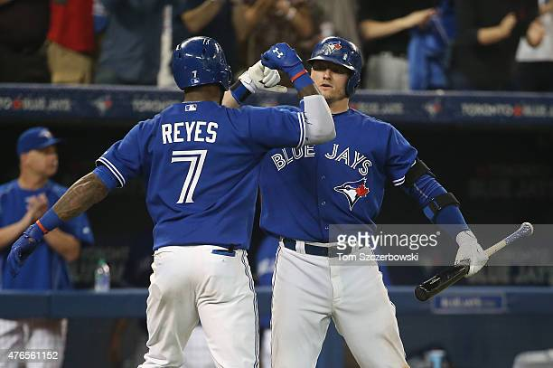 Jose Reyes of the Toronto Blue Jays is congratulated by Josh Donaldson after hitting a solo home run in the seventh inning during MLB game action...