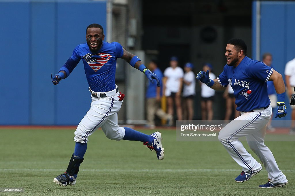 Jose Reyes #7 of the Toronto Blue Jays is congratulated by <a gi-track='captionPersonalityLinkClicked' href=/galleries/search?phrase=Melky+Cabrera&family=editorial&specificpeople=453444 ng-click='$event.stopPropagation()'>Melky Cabrera</a> #53 in the 10th inning after hitting the game-winning single during MLB game action against the Tampa Bay Rays on August 23, 2014 at Rogers Centre in Toronto, Ontario, Canada.