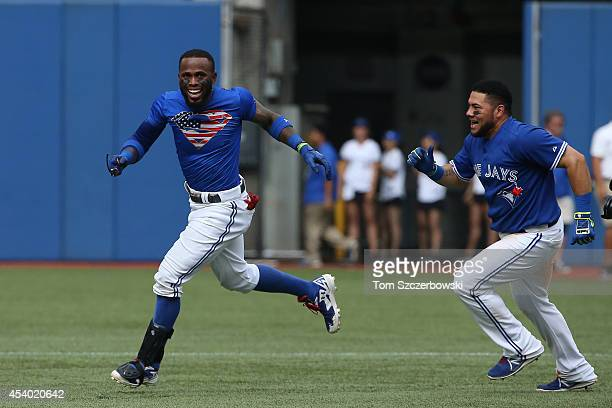 Jose Reyes of the Toronto Blue Jays is congratulated by Melky Cabrera in the 10th inning after hitting the gamewinning single during MLB game action...