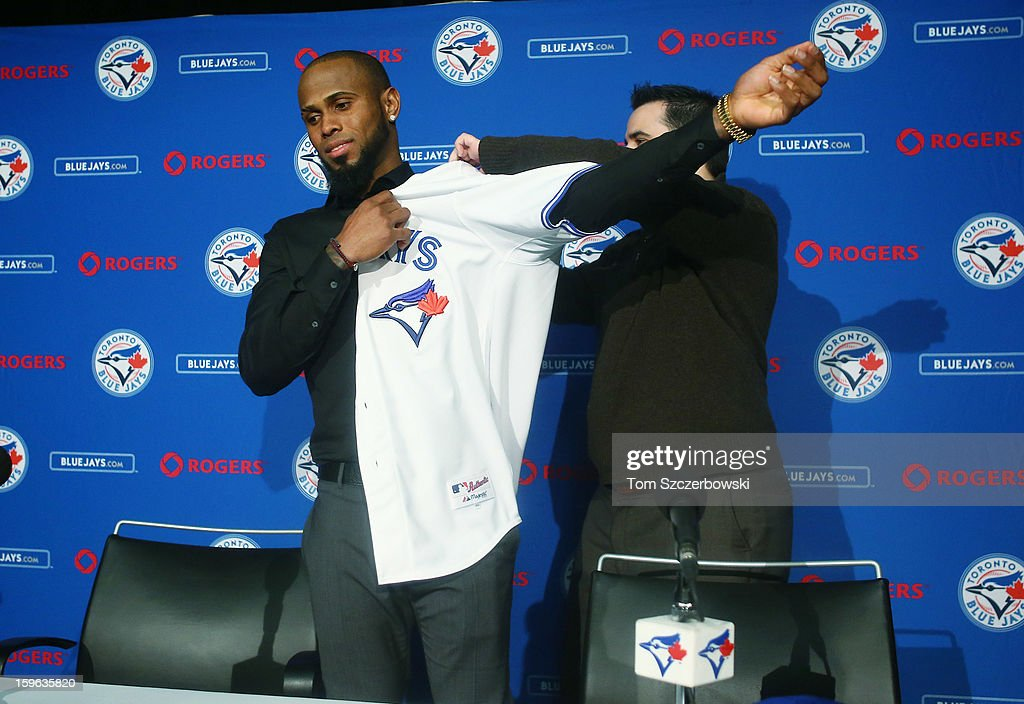 Jose Reyes #7 of the Toronto Blue Jays puts on his jersey before being introduced at a press conference with general manager <a gi-track='captionPersonalityLinkClicked' href=/galleries/search?phrase=Alex+Anthopoulos&family=editorial&specificpeople=6770623 ng-click='$event.stopPropagation()'>Alex Anthopoulos</a> at Rogers Centre on January 17, 2013 in Toronto, Ontario.