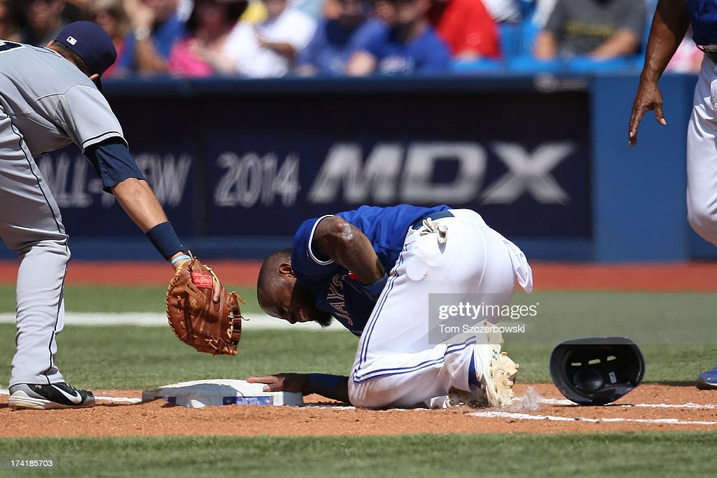 Jose Reyes #7 of the Toronto Blue Jays reacts in pain after being hit by a pick-off throw in the fifth inning during MLB game action against the Tampa Bay Rays on July 21, 2013 at Rogers Centre in Toronto, Ontario, Canada.
