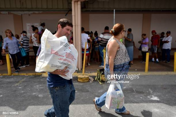 Jose Rodriguez walks while carrying food he bought in a supermarket in Humacao in the east of Puerto Rico on September 27 2017 The US island...