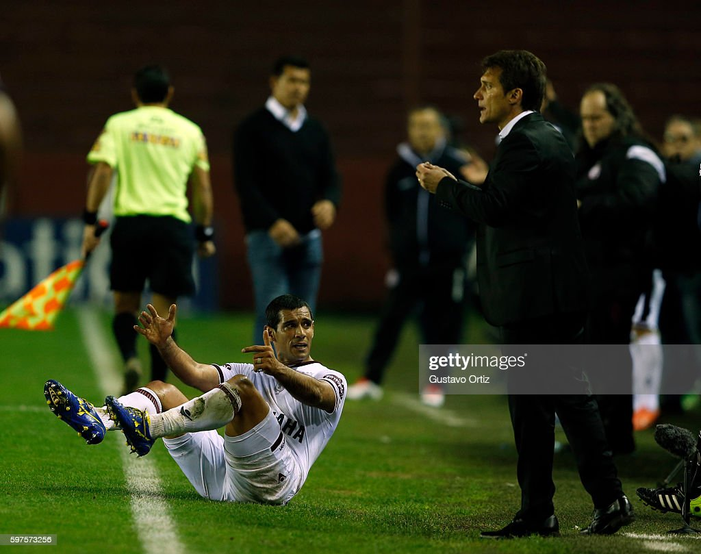 Jose Sand of Lanus lies on the ground next to Guillermo Barros Schelotto coach of Boca during a match between Lanus and Boca Juniors as part of first...