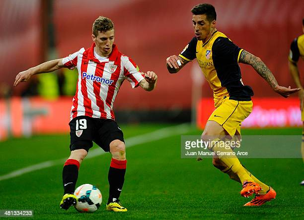 Jose Sosa of Atletico de Madrid competes for the ball with Iker Muniain of Athletic Club during the La Liga match between Athletic Club de Bilbao and...