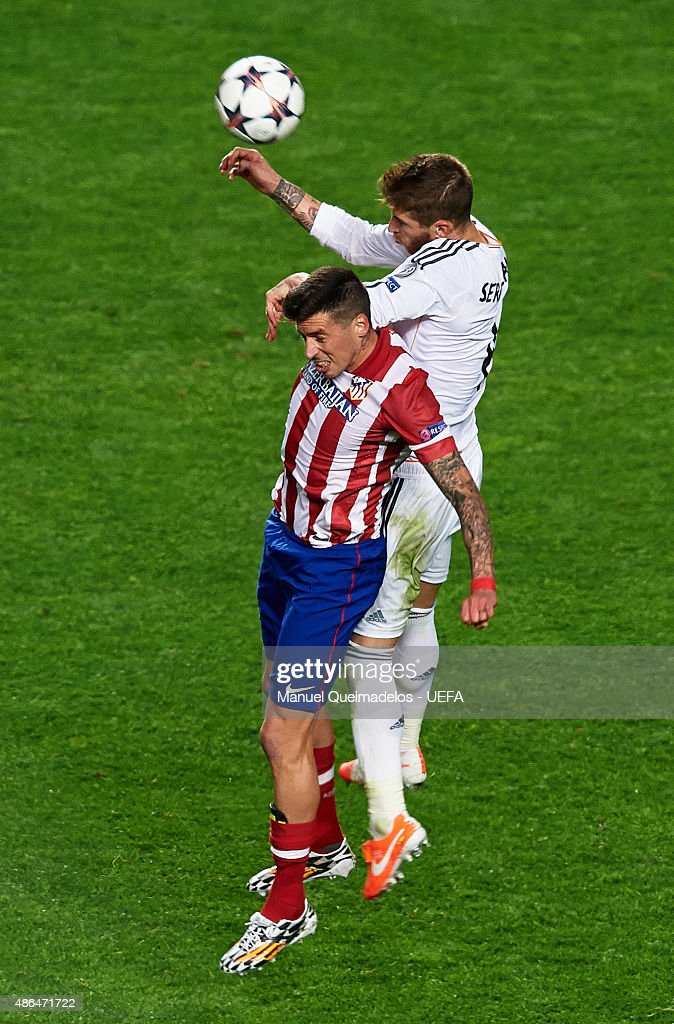 Jose Sosa of Club Atletico de Madrid jumps for a header with Sergio Ramos of Real Madrid during the UEFA Champions League Final between Real Madrid...