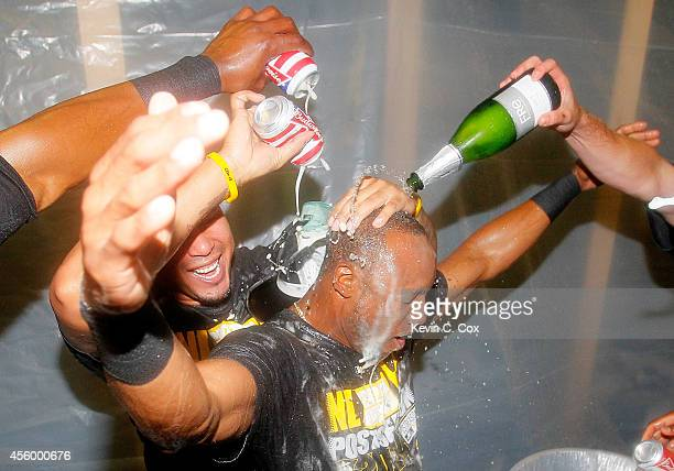 Jose Tabata douses Starling Marte of the Pittsburgh Pirates with beer as they celebrate clinching a National League playoff spot after their 32 win...
