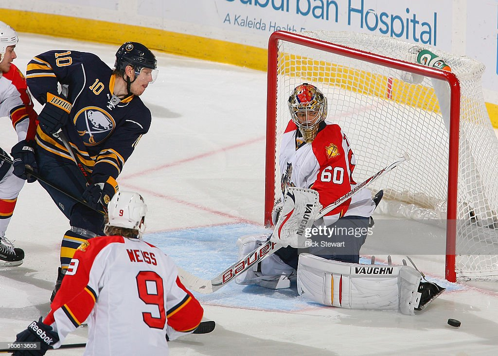Jose Theodore #60 of the Florida Panthers deflects a shot as Christian Ehrhoff #10 of the Buffalo Sabres skates in at First Niagara Center on February 3, 2013 in Buffalo, New York. Florida won 4-3.