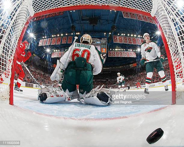 Jose Theodore of the Minnesota Wild looks on as Darren Helm of the Detroit Red Wings scores a goal during an NHL game at Joe Louis Arena on April 3...