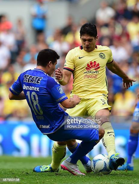 Jose Torres of Tigres vies for the ball with America's Javier Guemez during their Mexican Apertura tournament football match at the Azteca stadium on...
