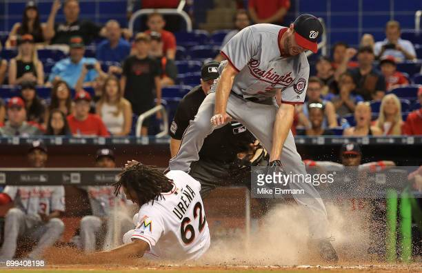 Jose Urena of the Miami Marlins scores the tying run in the eighth inning sliding under the tag from Stephen Strasburg of the Washington Nationals on...