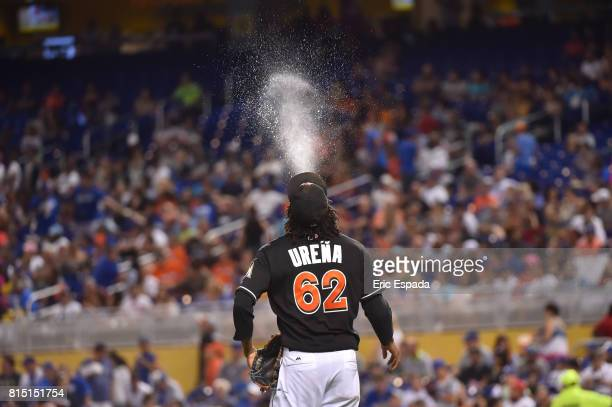 Jose Urena of the Miami Marlins spits water in the air on his way to the mound before the start of the third inning against the Los Angeles Dodgers...