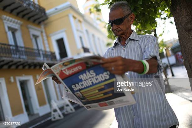 Jose Vasquez reads a newspaper with a Spanish headline that reads 'more sacrifices' a day after the speech Puerto Rican Governor Alejandro Garcia...