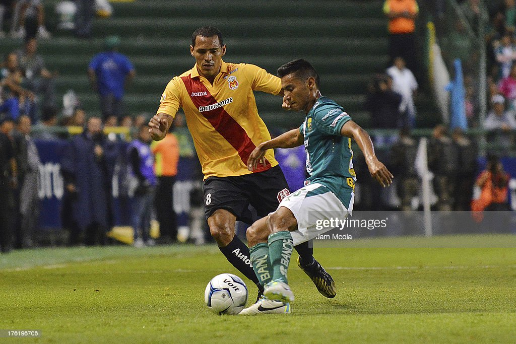 Jose Vazquez (R) of Leon struggles for the ball with Aldo Leao Ramirez (L) of Morelia during the Apertura 2013 Liga Bancomer MX at Nou Camp Stadium on August 10, 2013 in Leon, Mexico.