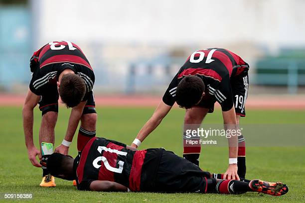 JoseEnrique Rios Alonso and Elias Abouchabaka of Germany assist CharlesJesaja Herrmann on the pitch during the UEFA Under16 match between U16 France...