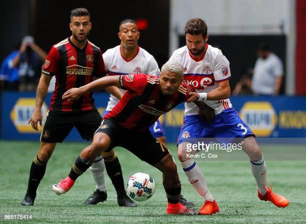 Josef Martinez of Atlanta United is challenged by Drew Moor of Toronto FC at MercedesBenz Stadium on October 22 2017 in Atlanta Georgia