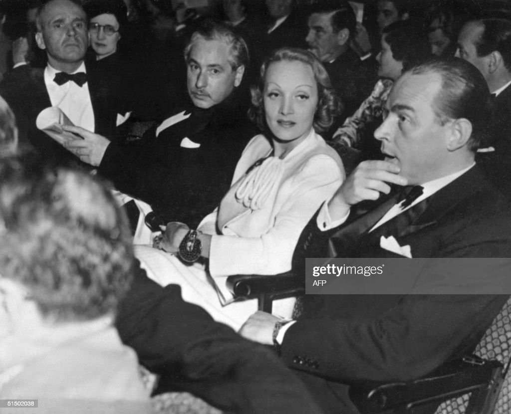 Josef von Sternberg (2nd-L), originally Jonas Stern (1894-), Austrian-born film director, German-born actress Marlene Dietrich and her friend German writer Erich Maria Remarque (R), chat 28 May 1939 before screening a movie in Hollywood Four Star Theater. Sternberg worked in silent films in Hollywood in the 1920s as scriptwriter, cameraman, and director, but went to Germany to make his most famous film, 'Der blaue Engel' (1930, The Blue Angel), with Marlene Dietrich.