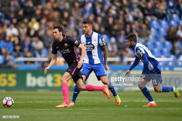 Joselu of RC Deportivo La Coruna competes for the ball with Sergio Busquets of FC Barcelona during the La Liga match between RC Deportivo La Coruna...