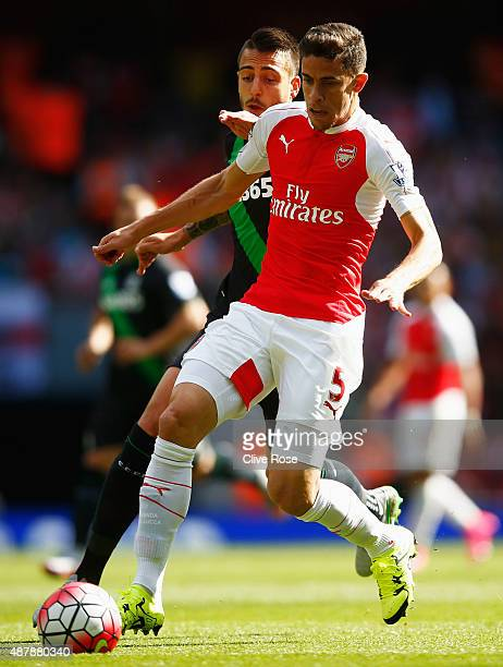 Joselu of Stoke City challenges Gabriel Paulista of Arsenal during the Barclays Premier League match between Arsenal and Stoke City at the Emirates...