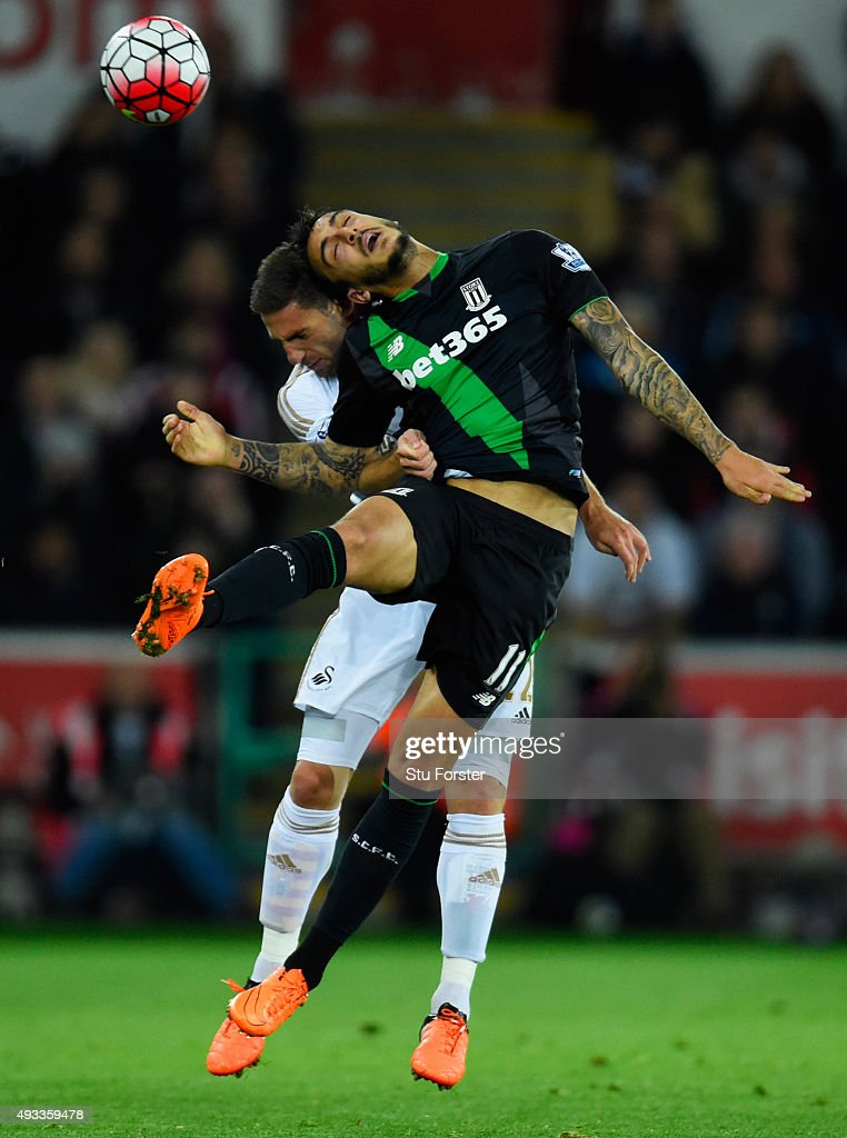 Joselu of Stoke City jumps for the ball with Angel Rangel of Swansea City during the Barclays Premier League match between Swansea City and Stoke City at Liberty Stadium on October 19, 2015 in Swansea, Wales.