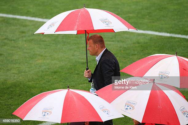 Josep Gombau of Adelaide stands with an umbrella in the rain as he looks on during the round six ALeague match between Adelaide United and the...