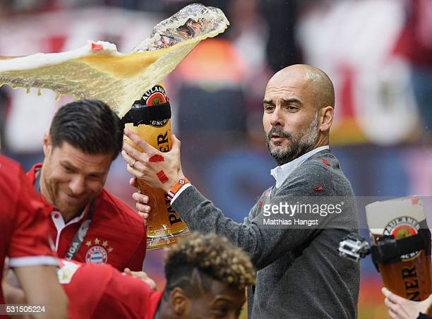 Josep Guardiola coach of Bayern Muenchen throws his beer after winning the Bundesliga match between FC Bayern Muenchen and Hannover 96 at Allianz...