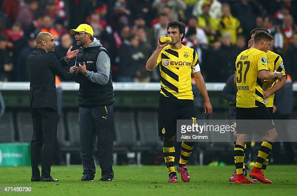 Josep Guardiola head coach of Bayern Muenche talks with Juergen Klopp head coach of Dortmund after the penalty shoot out during the DFB Cup semi...