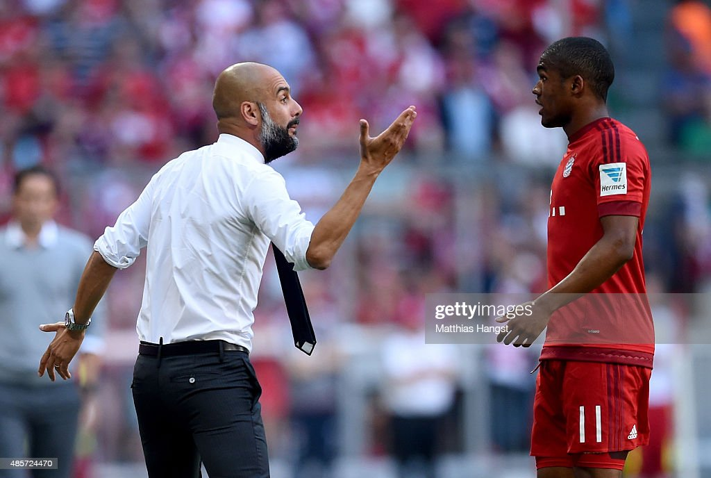 Josep Guardiola head coach of Bayern Muenchen gives instructions to Douglas Costa during the Bundesliga match between FC Bayern Muenchen and Bayer...