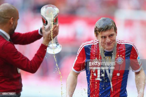 Josep Guardiola head coach of Bayern Muenchen poors beer over his player Toni Kroos as he celebrates with the Bundesliga championship trophy after...