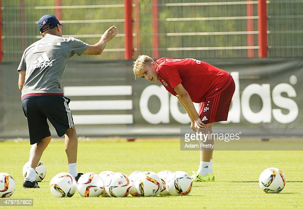 Josep Guardiola Head Coach of Bayern Muenchen speaks to Sinan Kurt during the FC Bayern Muenchen Training Session at the Bayern Munich training...