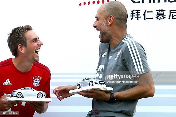 Josep Guardiola head coach of FC Bayern Muenchen smiles with his player Philipp Lahm after the Audi quattro Cup 2015 at Sheshan Golf Club during day...