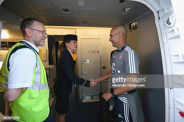 Josep Guardiola head coach of FC Bayern Muenchen talks to a Lufthansa air hostess as he board on the team flight to Beijing for the FC Bayern...