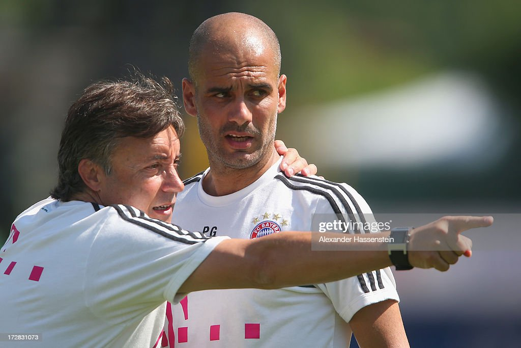 Josep Guardiola (R) head coach of FC Bayern Muenchen talks to his assistent coach Domenec Torrent during a training session at Campo Sportivo on July 5, 2013 in Arco, Italy.