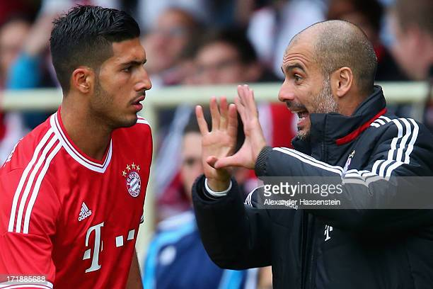 Josep Guardiola head coach of FC Bayern Muenchen talks to his player Emre Can during the friendly match between Fanclub Wildenau and FC Bayern...