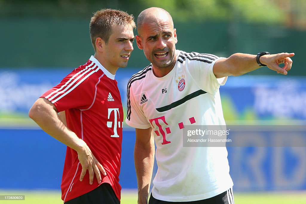 Josep Guardiola, head coach of FC Bayern Muenchen talks to his player Philipp Lahm during a training session at Campo Sportivo on July 5, 2013 in Arco, Italy.