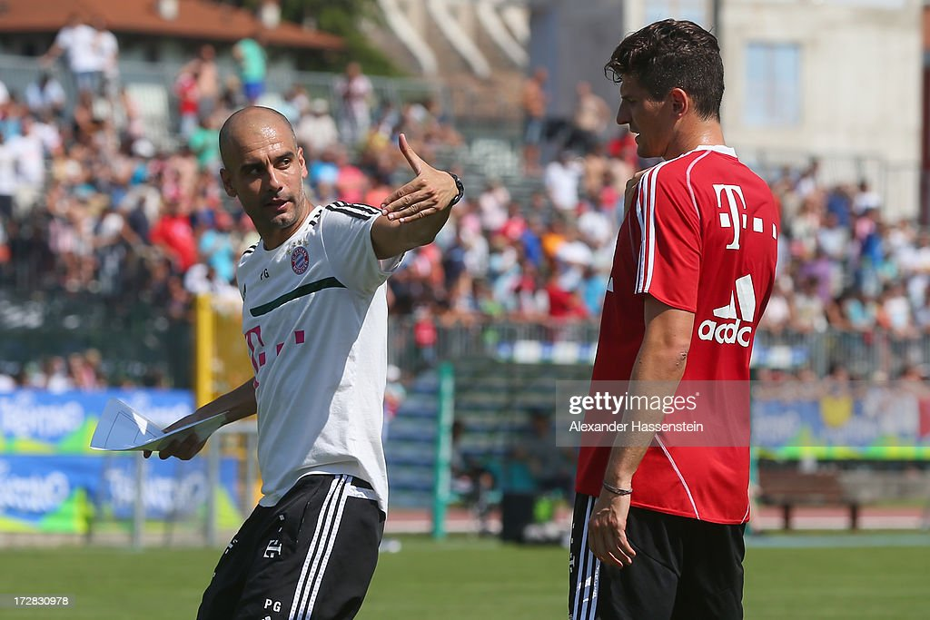 Josep Guardiola, head coach of FC Bayern Muenchen talks to his player Mario Gomez during a training session at Campo Sportivo on July 5, 2013 in Arco, Italy.