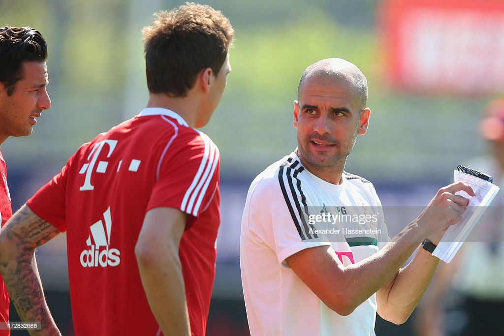Josep Guardiola, head coach of FC Bayern Muenchen talks to his players Mario Mandzukic and Claudio Pizarro (R) during a training session at Campo Sportivo on July 5, 2013 in Arco, Italy.