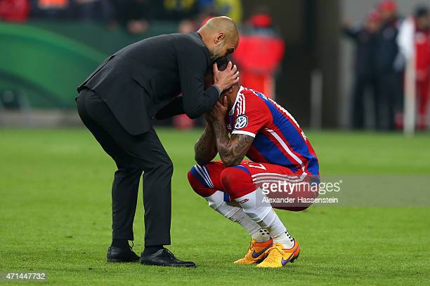 Josep Guardiola head coach of Muenchen reacts with his player Jerome Boateng after the DFB Cup Semi Final match between FC Bayern Muenchen and...