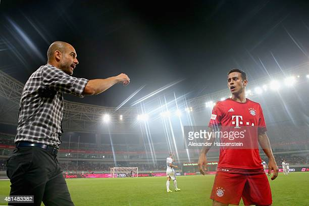 Josep Guardiola head coach of Muenchen talks to his player Thiago prior to the international friendly match between FC Bayern Muenchen and Inter...
