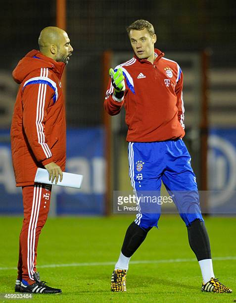 Josep Guardiola head coach of Muenchen talks to Manuel Neuer during a training session of FC Bayern Muenchen on December 4 2014 in Munich Germany