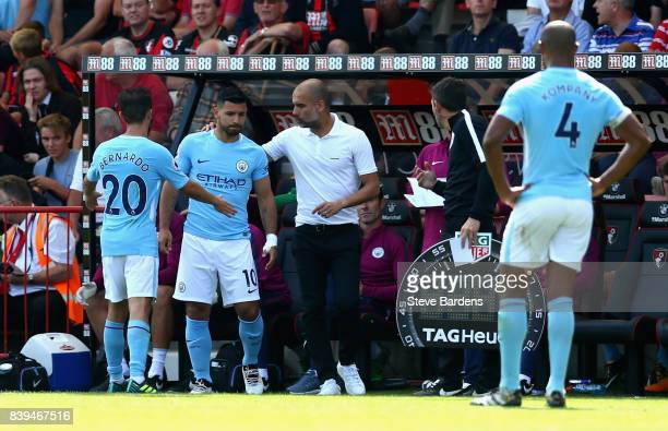 Josep Guardiola Manager of Manchester City gives instructions to Sergio Aguero of Manchester City as he prepares to come on during the Premier League...