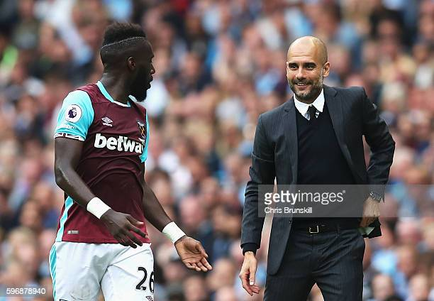 Josep Guardiola Manager of Manchester City smiles with Arthur Masuaku of West Ham United during the Premier League match between Manchester City and...
