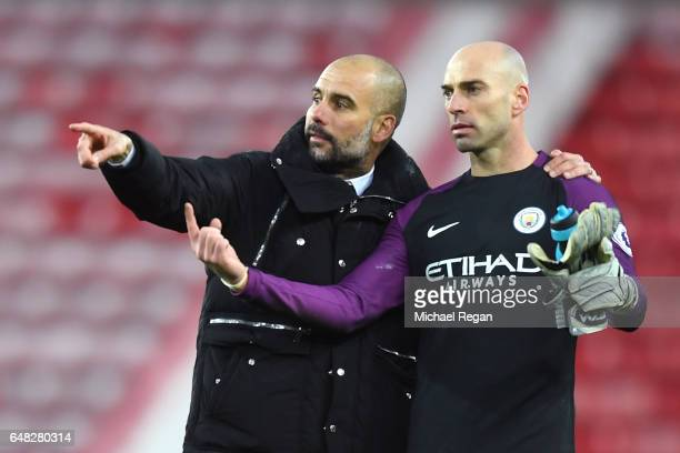 Josep Guardiola Manager of Manchester City speaks with Willy Caballero of Manchester City on the ptich after the Premier League match between...