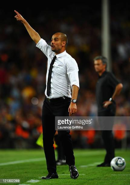 Josep Guardiola of Barcelona instructs his players in front of Jose Mourinho of Real Madrid during the Super Cup second leg match between Barcelona...