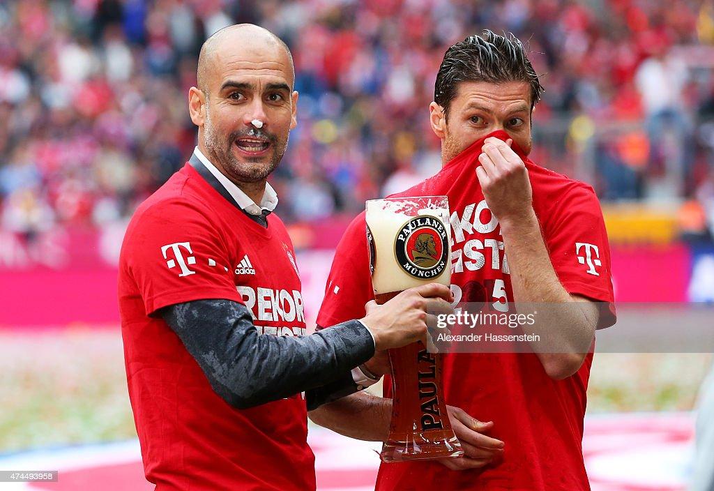 Josep Guardiola the head coach of Bayern Muenchen and Xabi Alonso of Bayern Muenchen celebrate winning the league following the Bundesliga match...
